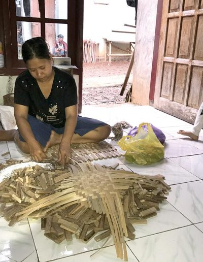 Suri's mother making reclaimed wood mats at home